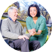 caregiver and senior man in wheel chair smiling
