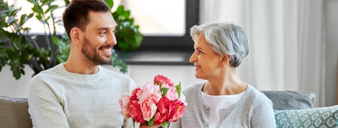 adult man gives flower to senior woman smiling