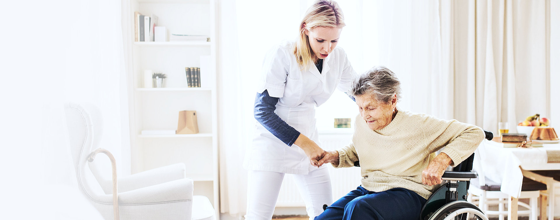 caregiver assisting senior woman in wheelchair