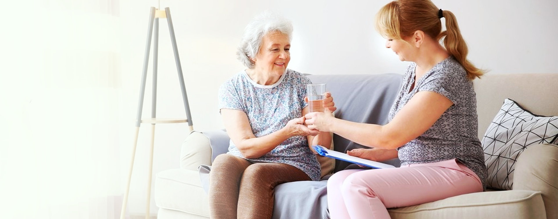 adult woman give a glass of water to senior woman