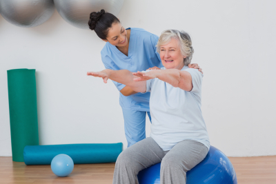 physical therapist assisting senior woman balancing exercise ball