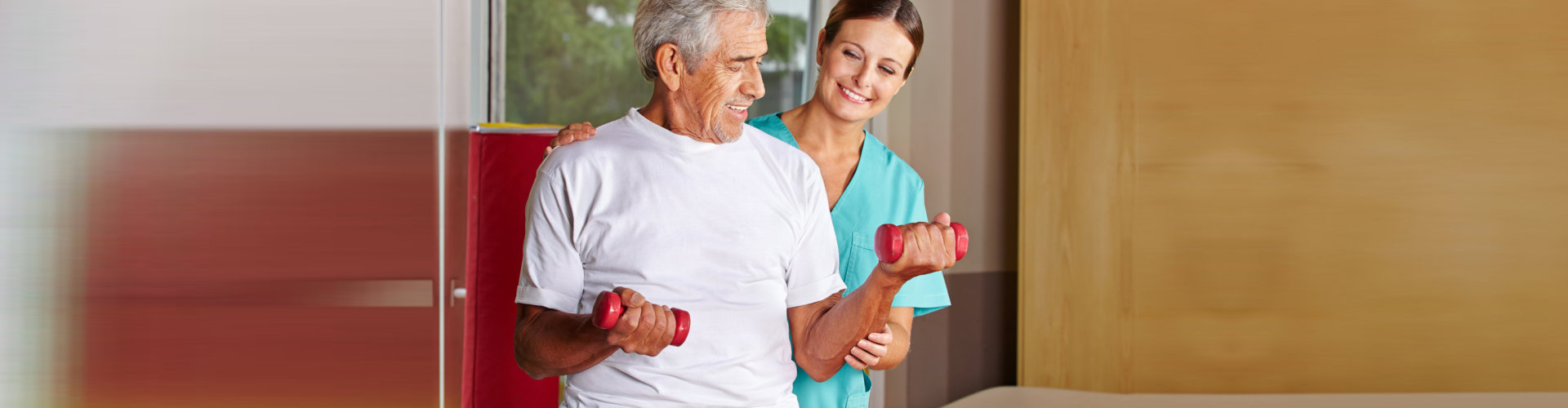 senior man with dumbbells assisting by the occupational therapist
